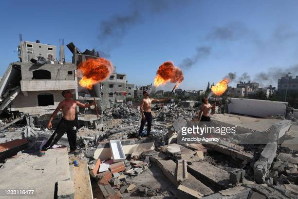Gazan friends make a fire-breating demonstration on the rubble of destroyed buildings targeted by Israeli attacks, to draw attention to the ruins in...