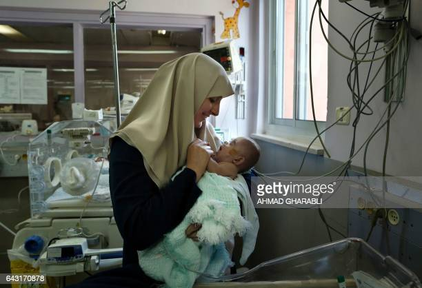 Gazan Jumana Daoud carries her 7monthold daughter Maryam at Makassed Hospital in Israeliannexed east Jerusalem on February 20 as they meet for the...