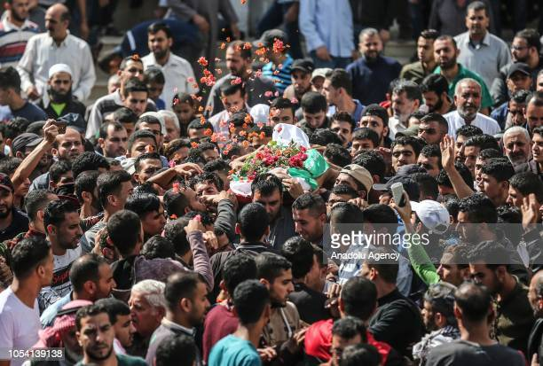 Gazans throw up flowers over the dead body of Ahmad Said Abu Lebde who was killed after Israeli soldiers intervened in Great March of Return...