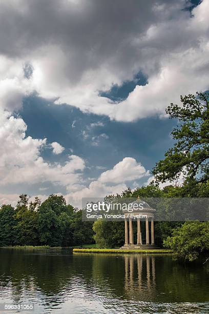 Gazebo Amidst Lake And Trees Against Cloudy Sky