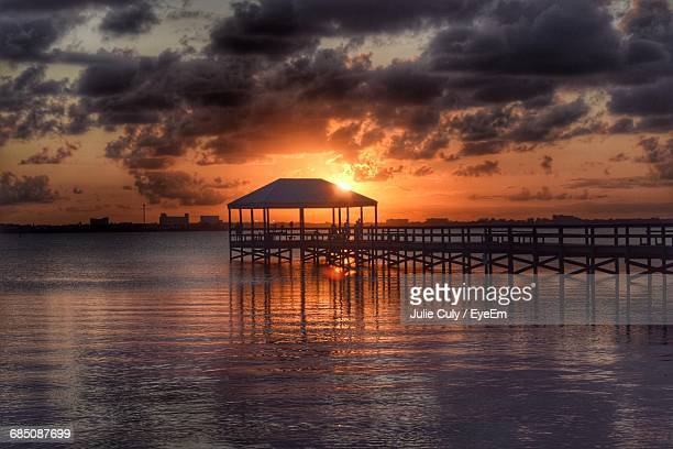 gazebo on pier at sea against cloudy sky during sunset - julie culy stock pictures, royalty-free photos & images