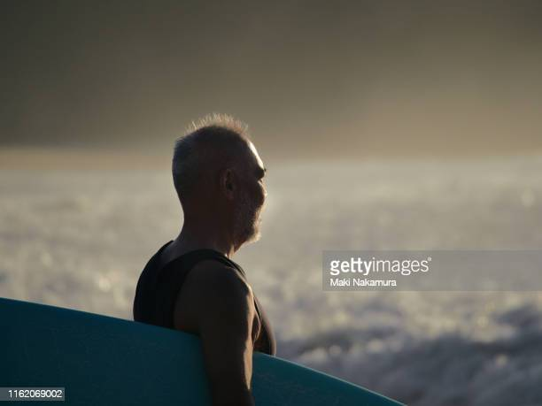 gazing at the sea holding a surfboard - generic location stock pictures, royalty-free photos & images