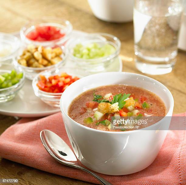 Gazpacho in soup bowl, surrounded by ingredients
