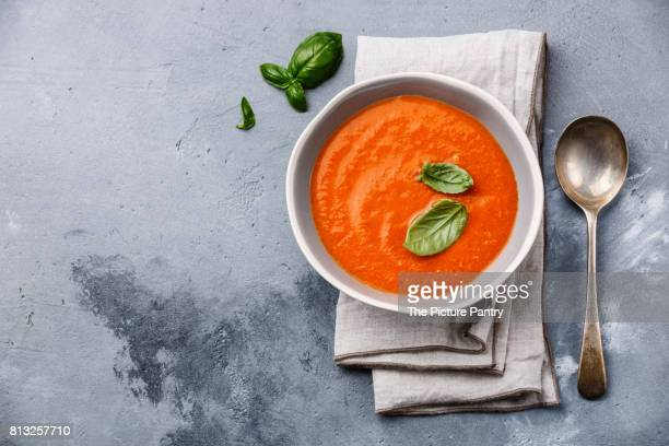 Gazpacho soup with green basil on grey concrete background