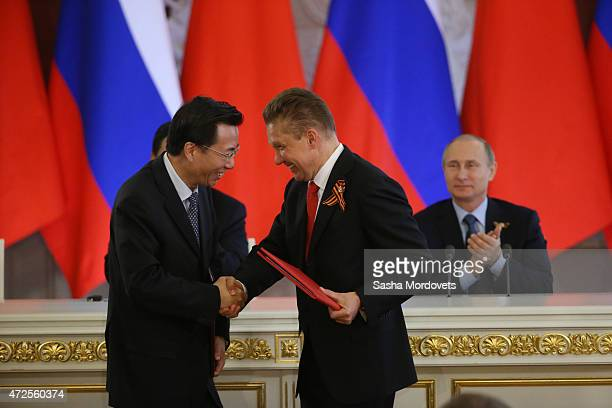 Gazprom's CEO Alexei Miller shakes hands with VicePresident of Chinese National Oil and Gaz Corporation Van Dunjing as they exchange documents during...