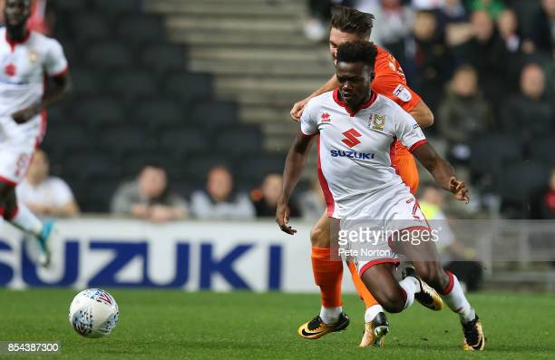 Gboly Ariyibi of Milton Keynes Dons attempts to move away from Matt Grimes of Northampton Town during the Sky Bet League One match between Milton...