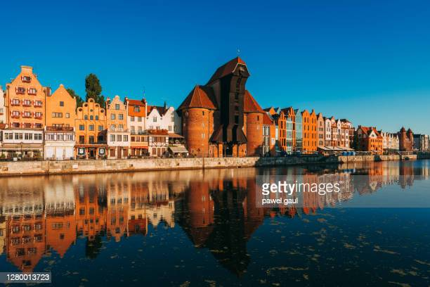 gdansk waterfront with crane gate and motlawa river at sunrise in poland - motlawa river stock pictures, royalty-free photos & images