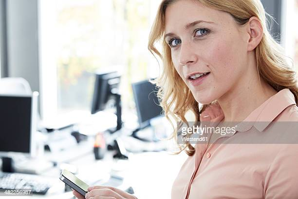 Gdermany, Neuss, Young woman in office using smart phone