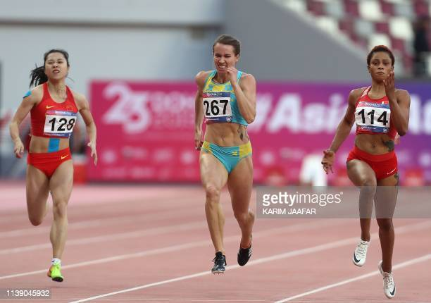 Ge Manqi of China Olga Safronova of Kazakhstan and Salwa Naser of Bahrain compete in the women's 200m race during the fourth day of the 23rd Asian...