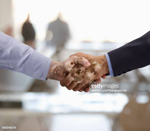 Gears overlaid on Caucasian businessmen shaking hands