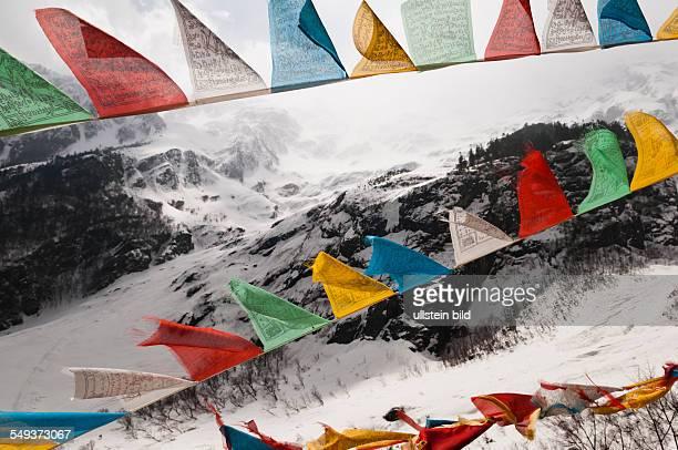 Gebetsfahnen im Schnee im Naturreservat Meili Xue Shan beim Mysterious Waterfall