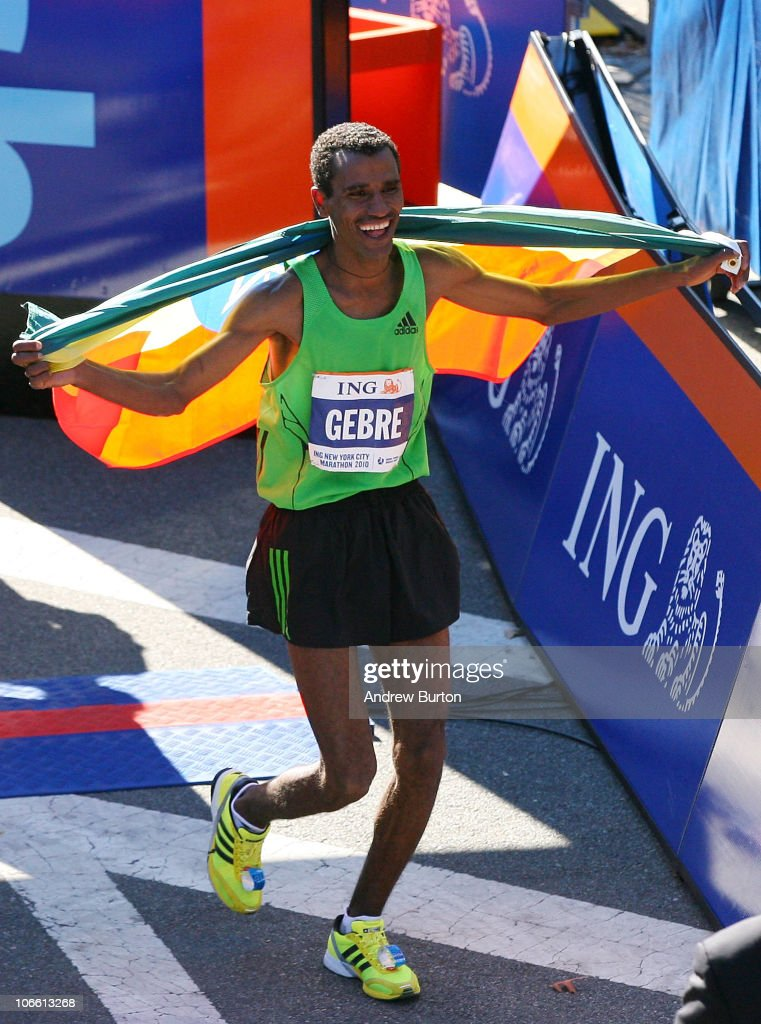 Gebre Gebremariam #14 of Ethiopia runs with the Ethiopian flag after winning the men's division of the 41st ING New York City Marathon on November 7, 2010 in New York City.