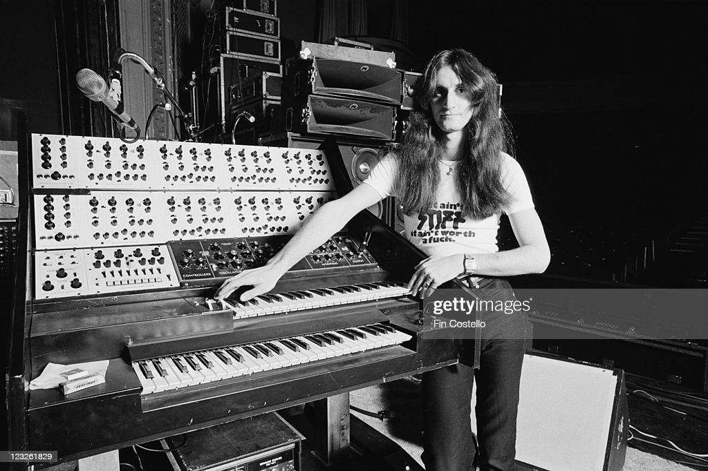Geddy Lee, singer and bassist with Canadian rock band Rush, poses beside a synthesizer during a soundcheck ahead of the band's gig at the Gaumont in Southampton, Hampshire, England, United Kingdom, 13 May 1979.