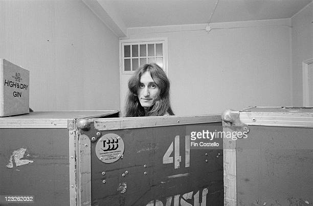 Geddy Lee singer and bassist with Canadian rock band Rush poses behind a luggage trunk backstage at the Gaumont in Southampton Hampshire England...