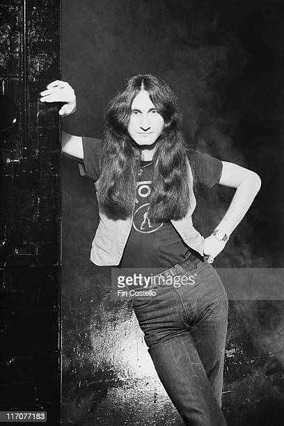 Geddy Lee singer and bassist with Canadian rock band Rush poses with one arm leaning on the wall beside him the other hand resting on his hip in a...