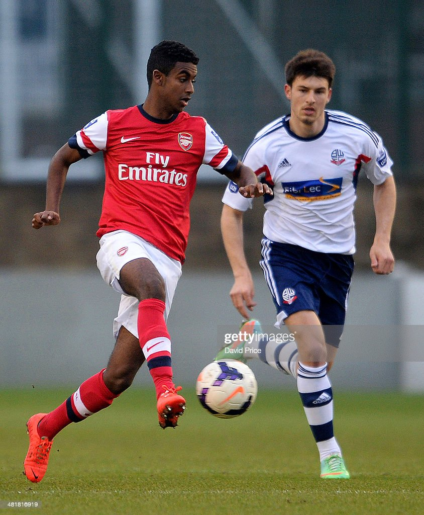 Gedion Zelalem of Arsenal races away from Luke Woodland of Bolton during the match between Bolton Wanderers U21 and Arsenal U21 in the Barclays Premier U21 League on March 31, 2014 in Lancaster, England.