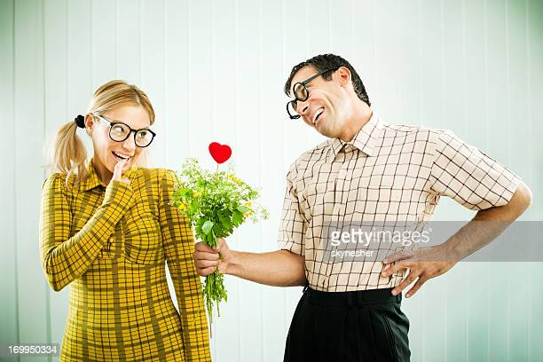 Geek man giving his girlfriend a Valentine present.