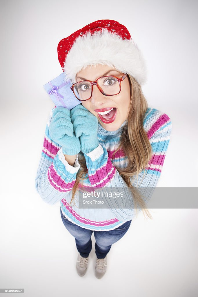 Geeky girl wearing Santas hat and glasses holding gift box : Stock Photo