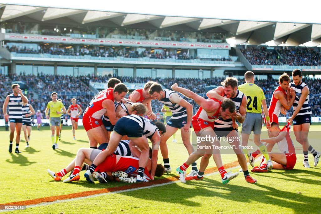 Geelong Cats and Sydney Swans players wrestle during the round six AFL match between the Geelong Cats and Sydney Swans at GMHBA Stadium on April 28, 2018 in Geelong, Australia.