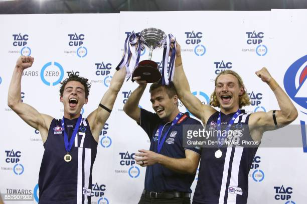 Geelong Falcons coach Daniel O'Keefe and captains James Worpel and Cooper Stephens celebrate with the trophy after winning during the TAC Cup Grand...