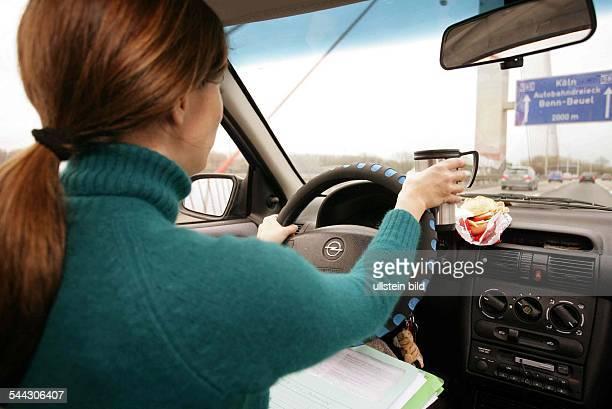 Gefahr im Straßenverkehr - Berufspendlerin frühstückt während der Fahrt auf der Autobahn mit Akten auf dem Schoß in ihrem PKW auf dem Weg zur Arbeit.
