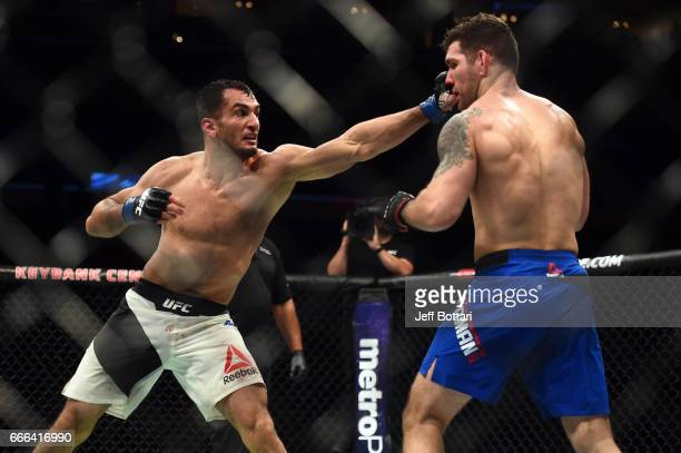 Gegard Mousasi of the Netherlands punches Chris Weidman in their middleweight bout during the UFC 210 event at the KeyBank Center on April 8 2017 in...