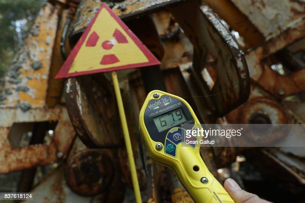 Geiger counter shows a reading of 679000 counts per minute near a metal claw contaminated with radioactivity in the ghost town of Pripyat not far...