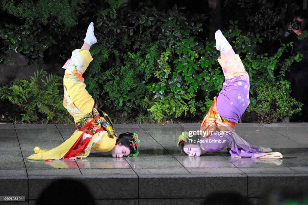 Geiko and Maiko perform the trick called 'Shachihoko' imitating the shape of the ornaments on the roof of Nagoya Castle during their performance at Kawabun-za on May 16, 2018 in Nagoya, Aichi, Japan.