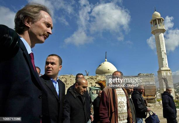 Geir Pedersen UN special coordinator for Lebanon Hezbollah deputy Hassan Fadlallah and other officials walk past a heavily damaged mosque during...