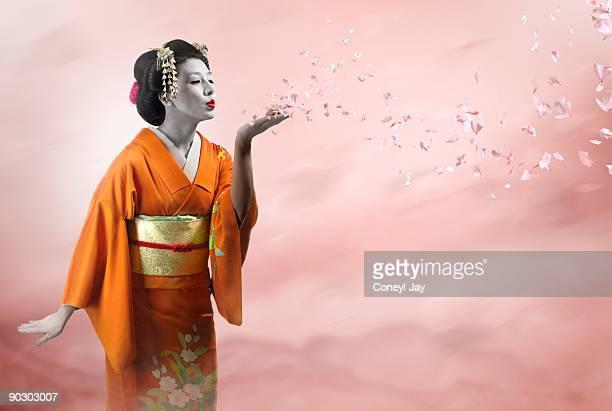 Geisha blowing many cherry blossom petals