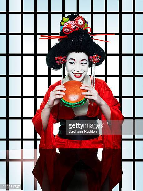 Geisha girl eating a huge hamburger