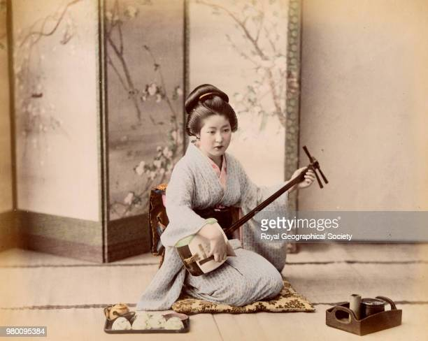 Geisha girl playing shamisen Japan 1908
