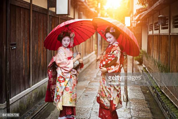 Geisha girls holding red umbrellas on footpath