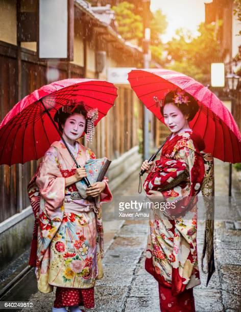 Geisha girls holding red umbrellas on street