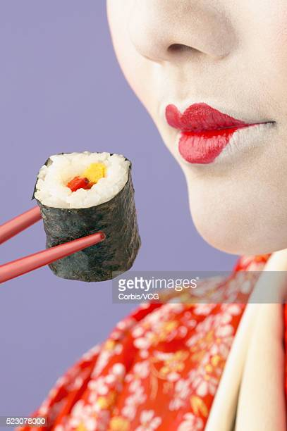 Geisha Holding Sushi with Chopsticks