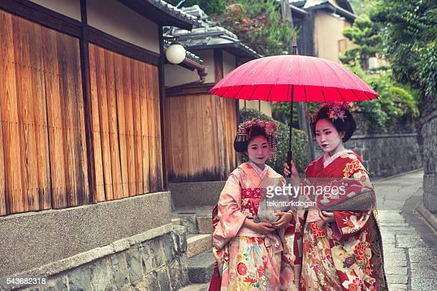 geisha maiko girls at narrow streets of oldtown kyoto japan - stadsdeel stockfoto's en -beelden