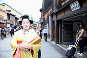 Geisha standing alone among a crowd of pedestrians in Gion