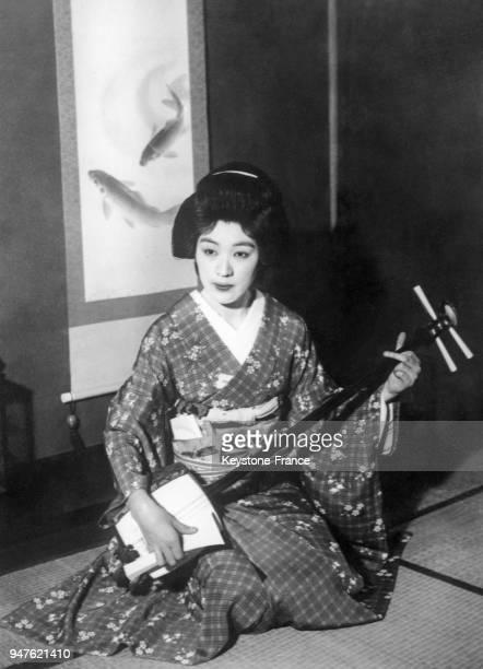 Geisha vêtue du costume traditionnel photographié avec l'instrument de musique traditionnel shamisen au Japon