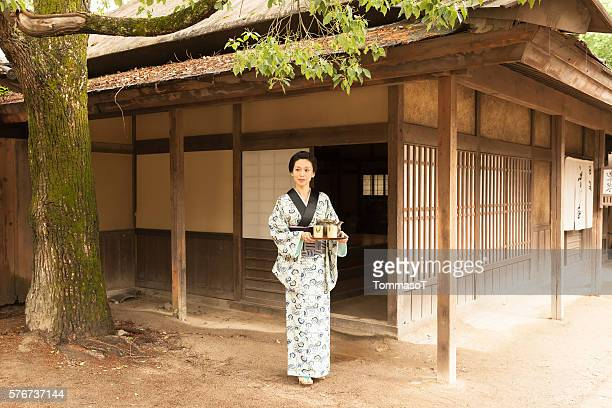 Geisha with tea tray outside a traditional japanese house