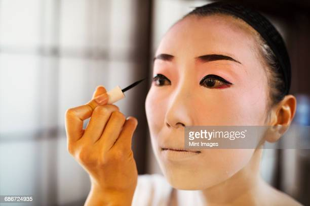 geisha woman with traditional white face makeup painting on heavy eyeliner with a brush. - アイライナー ストックフォトと画像