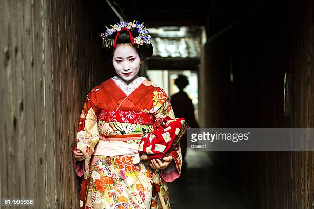 Geisha Women in Kimono Waiting in a Traditional Japanese Alleyway