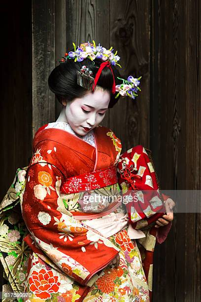 geisha women in kimono waiting in a traditional japanese alleyway - obi sash stock pictures, royalty-free photos & images