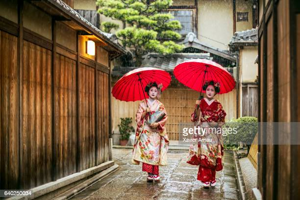 Geishas holding red umbrellas during rainy season