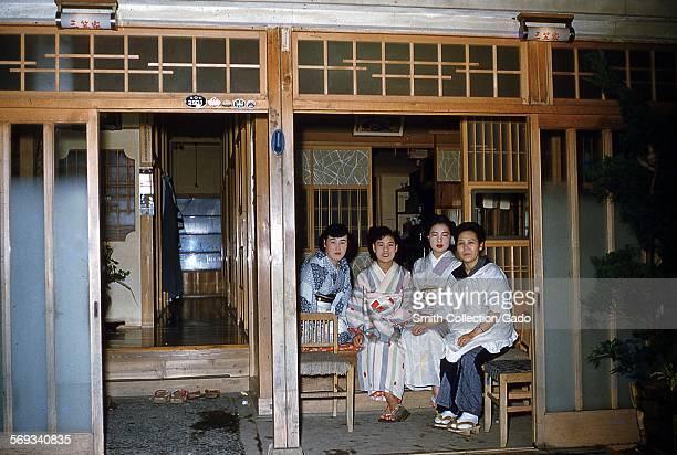 Geishas wearing kimonos sitting on chairs in a doorway, Japan, 1950.