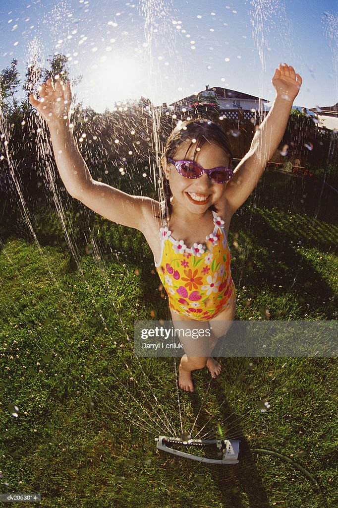 Gel Effect Shot of a Young Girl Wearing a Swimming Costume, Being Sprayed with Water From a Garden Sprinkler : Stock Photo