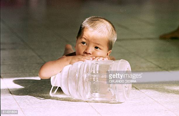 Gelber Nunez a twoyearold refugee from Hurricane Mitch rests while holding onto a bottle of water treated to eliminate possible cholera contamination...