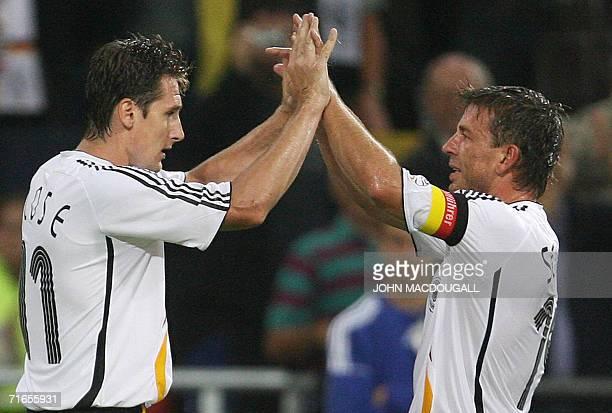 Gelsenkirchen, GERMANY: German forward Miroslav Klose celebrates with German midfielder Bernd Schneider after Klose scored his team's third goal...