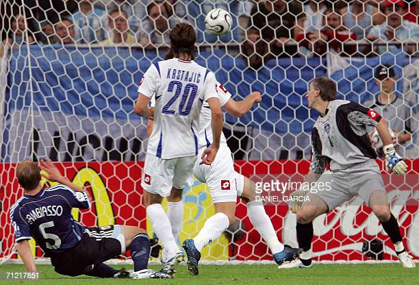 Serbia and Montenegro's goalkeeper Dragoslav Jevric misses a kick from Argentinian midfielder Esteban Cambiasso as Serbia and Montenegro's forward...