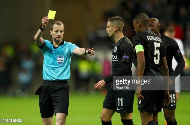 Gelson Fernandes of Eintracht Frankfurt is shown a yellow card by referee William Collum during the UEFA Europa League Round of 16 First Leg match...