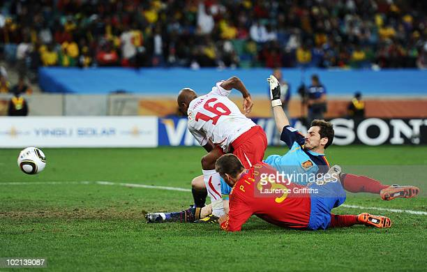 Gelson Fernandes of Switzerland breaks through Gerard Pique and Iker Casillas of Spain to score the first goal during the 2010 FIFA World Cup South...